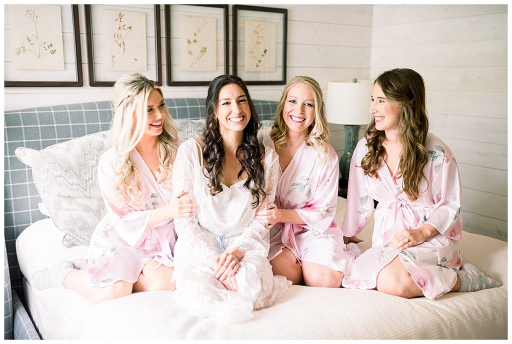 bride with bridesmaids on bed before wedding ceremony